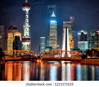 Nocturne view at Pudong with famous skyscraperand  towers. In foreground illuminated bridge reflection in Suzhou Creek water.