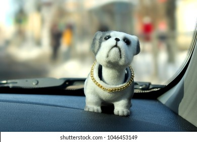 A nodding toy dog on the dashboard of a car on a window background