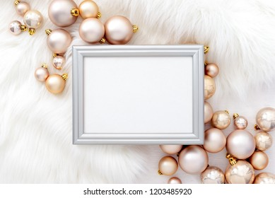 Noel or Christmas feminine social media background with a space for a text in a frame lying down on a white faux fur, decorated with  golden and pale pink balls