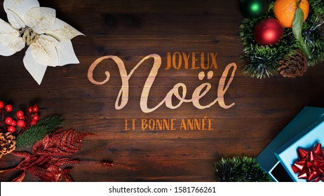 """""""Joyeux Noel et Bonne Anne"""" t.i. Merry Christmas and Happy New Year in French language on a wooden background with decoration horizontal view for social media and website home and diary pages"""