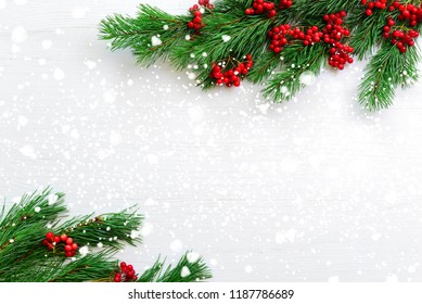 Noel flat lay composition with fir branches and red berries lying on a light wooden background covered with a snow,view from above, blank space for a text