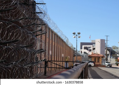 Nogales, Arizona / US - December 20, 2019: Looking west along razor wire and bollard style border wall on the US-Mexico border toward the Morley Gate Port of Entry. 5165