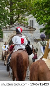 Nogent le Rotrou, France- May 19, 2012: A group of people dressed in medieval costumes ride horses at the entrance in Saint Jean Castle in Nogent le Rotrou, during  a historical reenactment festival