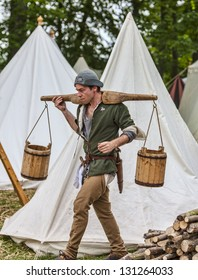NOGENT LE ROTROU,FRANCE,MAY19 :Unidentified water-carrier walking with empty water-carts on his shoulder between tents during a reenactment festival on May 19 2012 in Nogent le Rotrou, France.