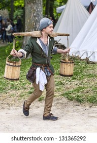 NOGENT LE ROTROU,FRANCE,MAY19 :Unidentified water-carrier walking with full water-carts on his shoulder between tents during a reenactment festival on May 19 2012 in Nogent le Rotrou, France.