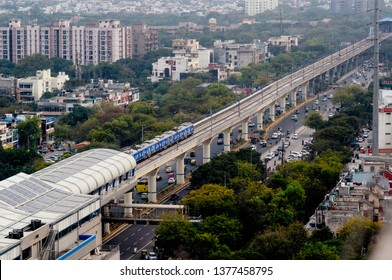Noida, Delhi, India - Circa 2019: Aerial shot of metro train arriving at an elevated metro station. Advertising on the metro train helps generate revenue for the public transport service that helps