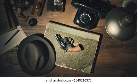 Noir 1950s style detective vintage desktop with revolver, fedora hat and telephone, flat lay