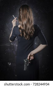Noir film style woman in dress holding cigarette standing back to camera. Female posing with gun. Black and white photography. Old fashion photo