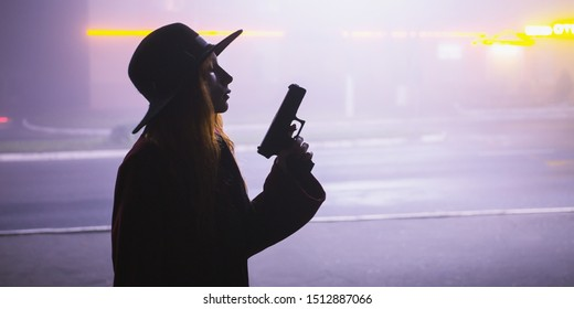 Noir gangster in hat with gun. Woman silhouette on background of night city in fog. Thick mist in dark scary evening city. Dark noir silhouette in hat on background of fog. Alone woman in mist.