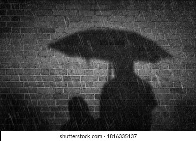Noir style autumn rainy night in city. Mother with children in rain protected with umbrella. Two people cast a shadow on old brick wall.