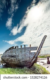 The Noirmoutier boats cemetery. The bow of the wreck of an old wooden fishing boat stands under a cloudy sky