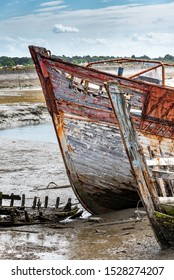 The Noirmoutier boats cemetery. The bow of the wreck of an old wooden fishing boat stranded on the mud at low tide.