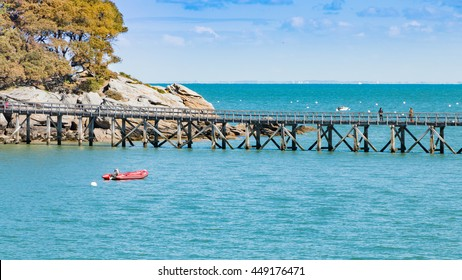 Noirmoutier, France - April 28, 2016 : wooden bridge on the sea with a boat