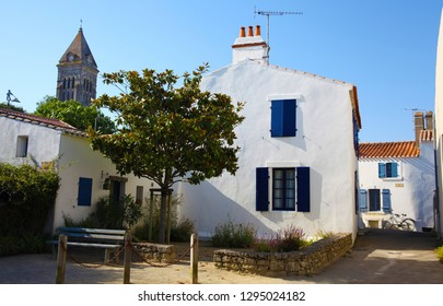 Noirmoutier island village, view on the city center with house facade with blue shutters, tree and church. Vendee, France