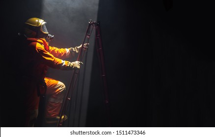 Noise and grain defocus of firefighter man in safety fire suit and oxygen tank on rescue duty climbing a ladder out of burning premises. Fireman into burning building area with smoke.