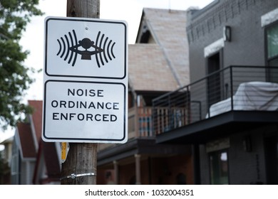Noise Ordinance Enforced sign with a symbol of person covering ears, posted with a neighborhood houses in the blurry background