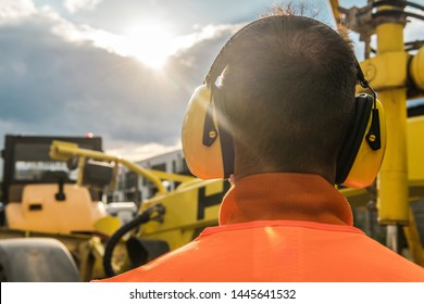 Noise Reduction Construction Equipment. Caucasian Worker with Hearing Protection Headphones.