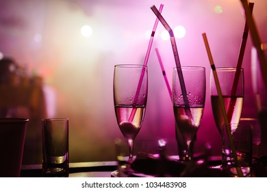 A noisy party in a nightclub with light music, on the table are stacks and glasses with champagne with stuck multi-colored straws