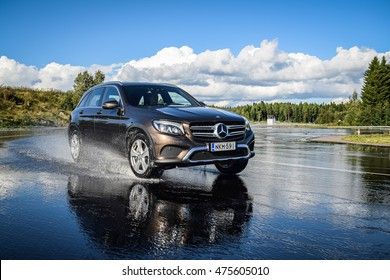 NOKIA, FINLAND - AUGUST 25, 2016: Summer tire test is held at the proving ground. Test-driver performs a wet handling test on Mercedes-Benz GLC to determine the tire which provides the best grip.