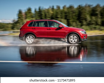 NOKIA, FINLAND - August 27, 2018: Red Volkswagen Tiguan drives on a slippery wet road on a prooving ground during tire tests.