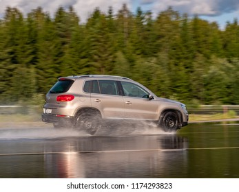 NOKIA, FINLAND - August 27, 2018: Volkswagen Tiguan drives on a slippery wet road on a prooving ground during tire tests.