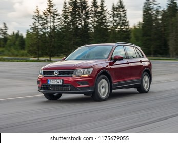NOKIA, FINLAND - August 27, 2018: Red A car by car photo of Volkswagen Tiguan drives on a asphalt road along a forest. Cloudy weather.