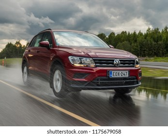 NOKIA, FINLAND - August 27, 2018: Red Volkswagen Tiguan drives on a wet road during cloudy summer day.