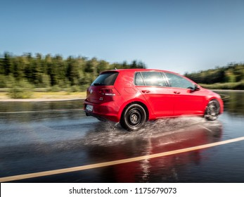 NOKIA, FINLAND - August 27, 2018: Red Volkswagen Golf drives on a slippery wet road on a prooving ground during tire tests.