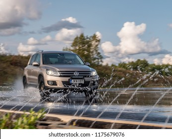 NOKIA, FINLAND - August 27, 2018: Volkswagen Tiguan drives on a slippery wet road on a prooving ground during tire tests. Watering jets in foreground.