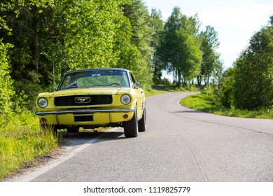NOKIA, FINLAND - JUNE 10 2018. Classic retro car parked in the countryside. 1966 Ford Mustang and curvy asphalt road.