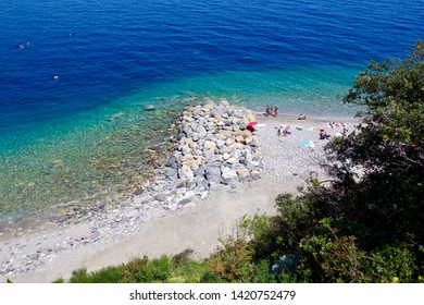 NOLI, LIGURIA, ITALY - JUNE 2019: aerial view of a beautiful rocky beach with clear and transparent sea water near the village of Noli in Liguria region,Italy