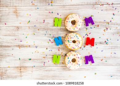 Nom Nom Nom Donuts on white wood background with sprinkles