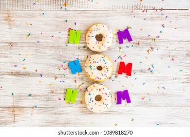 Nom Nom Nom silly donut saying on white wood background with colorful sprinkles and letters