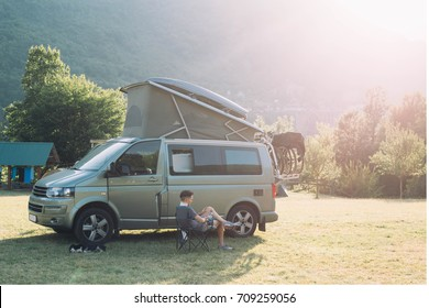Nomad adventurer with pet dog rest on camping site after long day of driving, sit on folding chair looks at mountains and sunset, next to camper van with bike rack