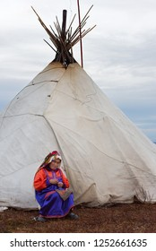 Nomad camp, Yamal peninsula, Russia-September 22, 2018: Housewife of nenets nomad tribe in national costume repairs a clothes in front of the family chum during autumn reindeer migration.