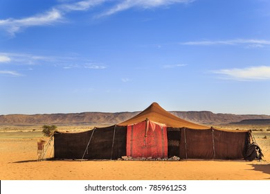 Nomad tents made of camel skin in the middle of the desert with mountains in the background