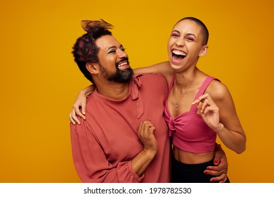 Non confroming friends standing together on yellow background. genderqueer man and woman smiling together.