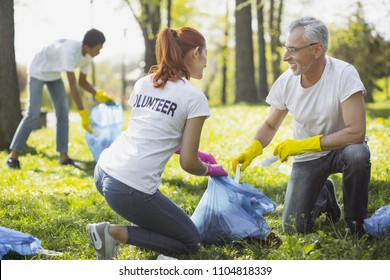Non profit volunteer. Vigorous two volunteers holding garbage bag and chatting