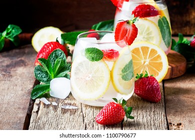 Non-alcoholic cocktail with strawberries, mint, lemon, soda and ice, old wooden background, selective focus