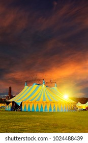 Nonamed circus tent under a warn sunset and chaotic sky without the name of the circus company which is cloned out and replaced by the metallic structure