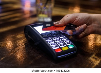Non-cash transaction - Credit card payment in a bar. Close up photo of woman hand paying with credit card.