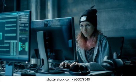Nonconformist Teenage Hacker Girl Attacks and Hacks Corporate Servers with Virus. Room is Dark, Neon and Has Many Displays and Cables.