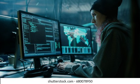 Nonconformist Teenage Hacker Girl Using her Computer to Organize Malware Attack on Global Scale. She's in Underground Secret Location Surrounded by Displays and Cables.