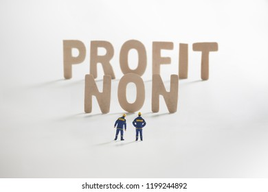 NONFROFIT word  with Miniature people: Engineer standing infront use as business concept.