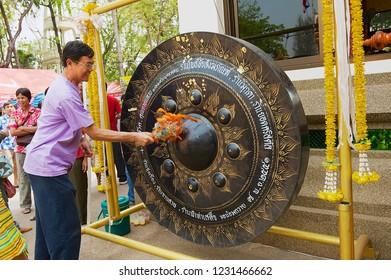 Nong Khai, Thailand - April 15, 2010: Unidentified man hits gong with a hammer visiting Wat Pho Chai buddhist temple in Nong Khai, Thailand.