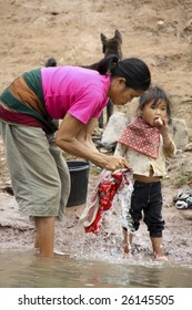 NONG KHIAW, LAOS - DEC 23 : A Lao woman with a little girl washes clothes by the river in Nong Khiaw, Laos December 23, 2008. Nong Khiaw is a village by Nam Ou River, surrounded by mountains and caves.