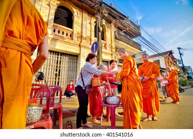 NONGKHAI - OCTOBER 27, 2015: People put food offerings in a Buddhist monk's alms bowl for virtue in the end of Buddhist Lent Day at Nongkhai Province, NorthEast of Thailand.