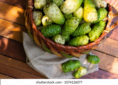 Noni basket and noni on Brown cloth on wooden table with nature background,Top view.