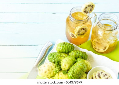 Noni fruit in the dish and noni slice  and noni juice with knife on green checkered fabric