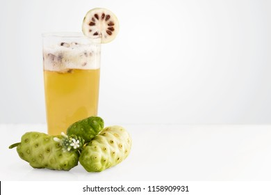 Noni fruit juice or Morinda Citrifolia and noni slice for health on the white table isolated on gray blackground with copy space for text. (with clipping path)